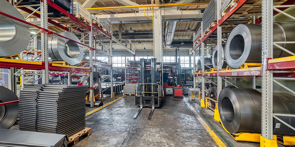 Tiered rack with sheet metal rolls. Internal warehouse of raw materials